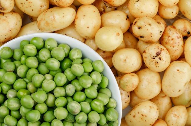 Grüne erbsen in einer weißen schüssel auf kartoffelwand, nahaufnahme.