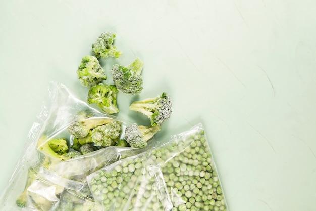 Grüne erbsen und brokkoli in transparenten beuteln auf hellgrün