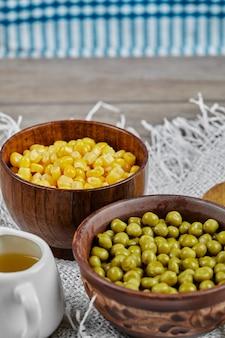 Grüne erbsen und maisbohnen in holzbechern.