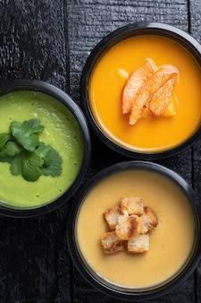 Grüne erbsencremesuppe, rote linsencremesuppe und ohne fleisch suppe aus gemüse in drei lebensmittelboxen