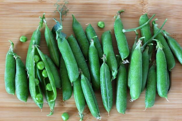Grüne erbsenschoten auf einem schneidebrett draufsicht gemüse frische lebensmittel