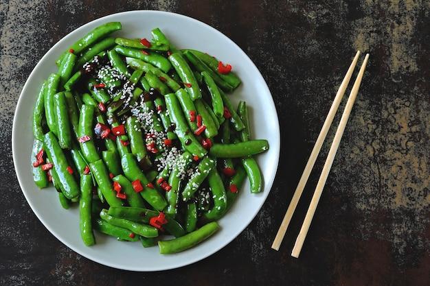 Grüne erbsenschoten mit chili und sesam. grüne hülsen im chinesischen stil.