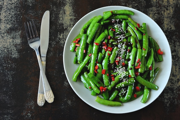 Grüne erbsenschoten mit chili und sesam.