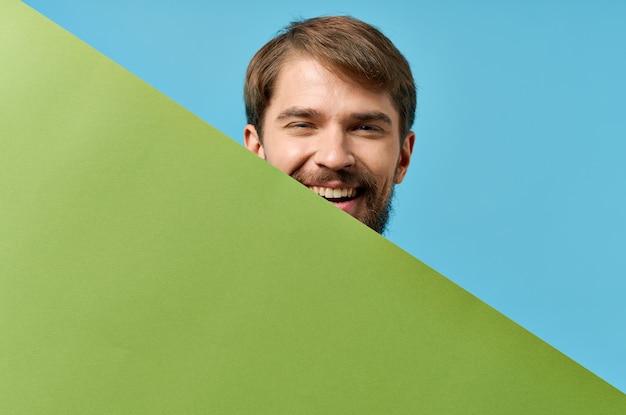Grüne fahne des gutaussehenden mannes in der hand leeres blatt blauen hintergrund