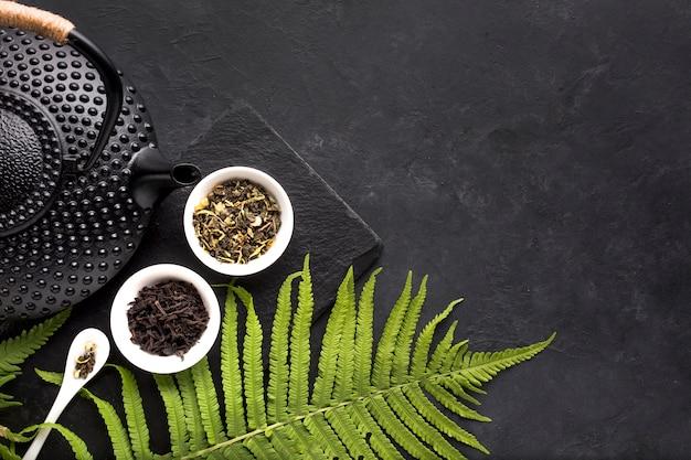 Grüne farnblätter und getrocknetes teekraut mit schwarzer teekanne auf schwarzem hintergrund