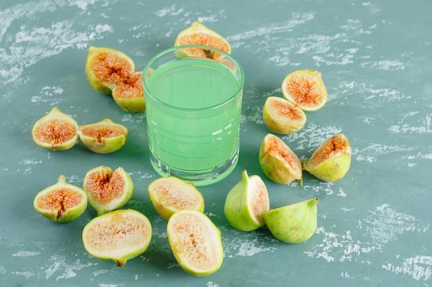 Grüne feigen mit glasgetränk draufsicht auf einer gipswand