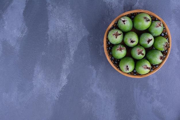 Grüne feijoa-früchte in einer holzschale auf blauem tisch.