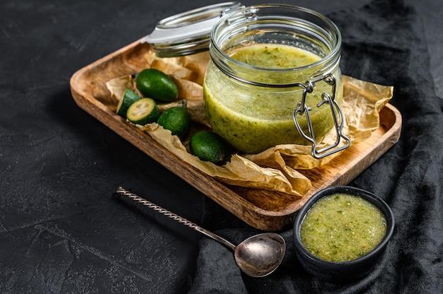 Grüne feijoa-marmelade auf einem hölzernen schneidebrett in einem glas. natürliches hausgemachtes dessert. schwarzer hintergrund. draufsicht
