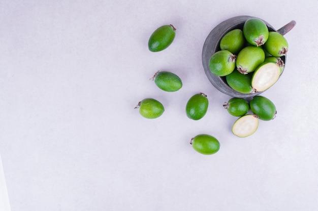 Grüne feijoas in einem metalltopf auf weißer oberfläche