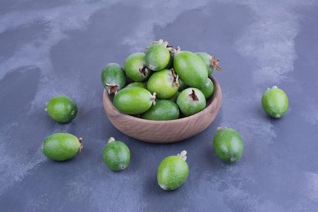 Grüne feijoas in einer holzschale auf blauer oberfläche