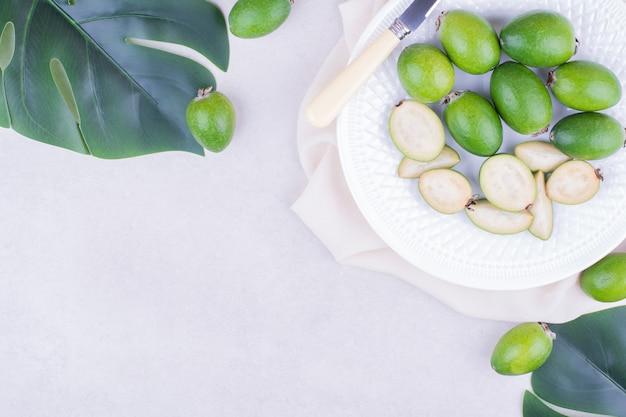 Grüne feijoas in einer weißen platte mit blättern herum.