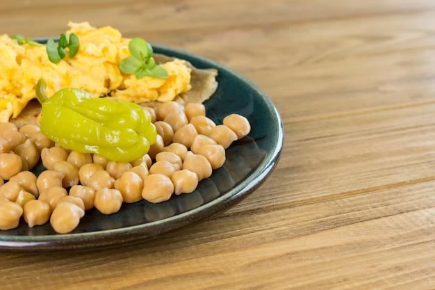 Grüne fermentierte grüne paprika und kichererbsen. rührei auf fladenbrot. grüne platte.