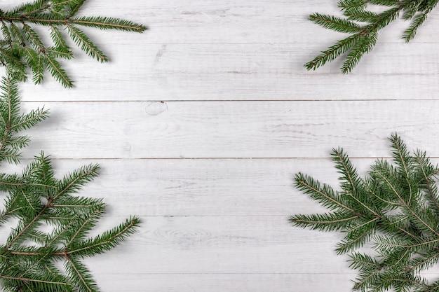 Grüne fichte verzweigt als rahmen auf weißem hölzernem hintergrund. weihnachtskonzept mit kopierraum