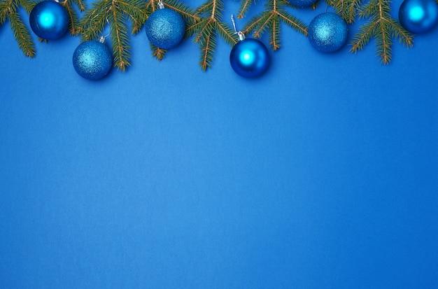 Grüne fichtenzweige, blaue glänzende weihnachtsbälle auf blau