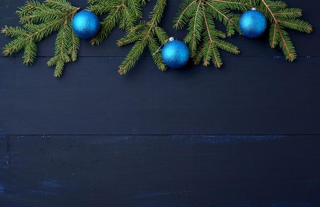 Grüne fichtenzweige und dunkelblaue glänzende weihnachtskugeln