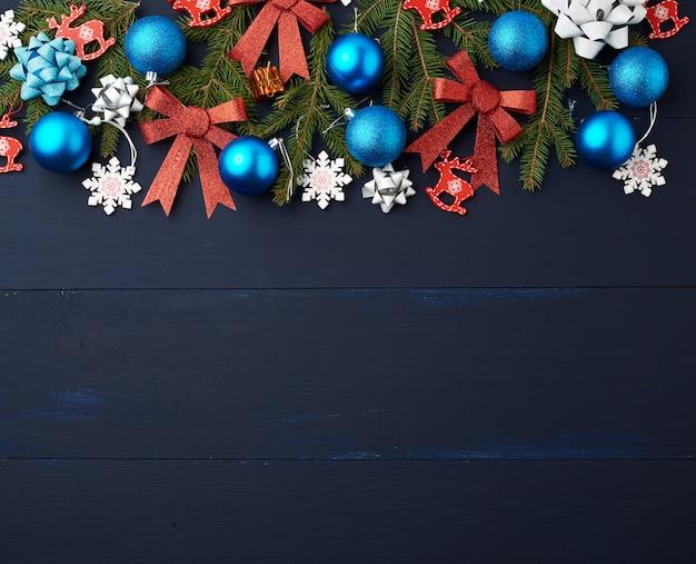 Grüne fichtenzweige, weihnachtsblaue und rosa bälle, rote glänzende bögen
