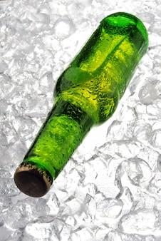 Grüne flasche bier auf eis
