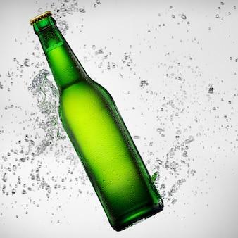 Grüne flasche bier, die in wasserspritzer fällt
