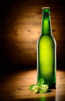 Grüne flasche bier und hopfen auf holz