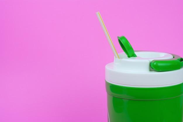 Grüne flasche für kaltes wasser auf rosa hintergrund.