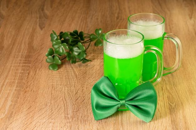 Grüne fliege, bier und blätter von kleeblatt auf holz