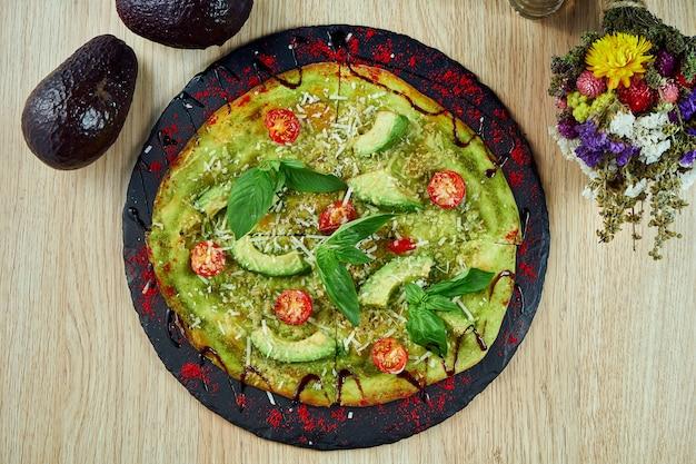 Grüne focaccia-pizza mit avocado, kirschtomaten, basilikum und parmesan auf einem schwarzen schieferbrett auf einem holztisch. draufsicht wohnung lag essen. italienische küche.