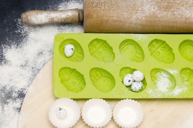 Grüne form des silikons für das backen von ostern-kleinen kuchen auf einem schwarzen hintergrund mit mehl