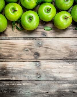 Grüne frische äpfel mit blättern. auf grauem holz.