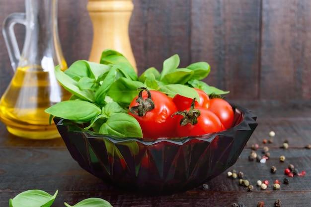 Grüne frische blätter von bio-basilikum und kleinen reifen tomaten, öl und pfeffer auf einem holztisch für eine gesunde ernährung.