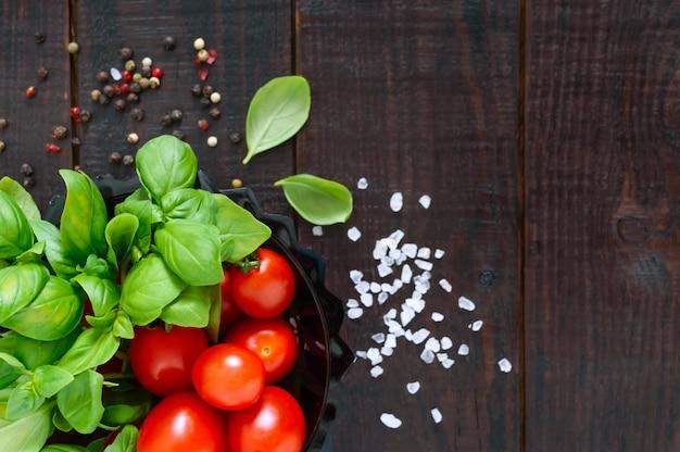 Grüne frische blätter von bio-basilikum und kleinen reifen tomaten und pfeffer auf einem holztisch für eine gesunde ernährung. draufsicht. freier speicherplatz für ihr projekt.