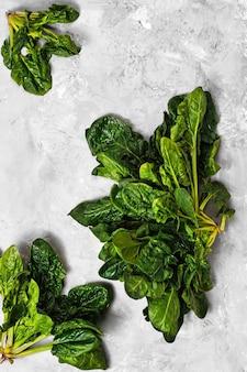 Grüne frische spinatblätter auf neutralem grauem beton