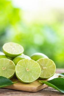 Grüne frische zitrone der scheibe auf holztischhintergrund