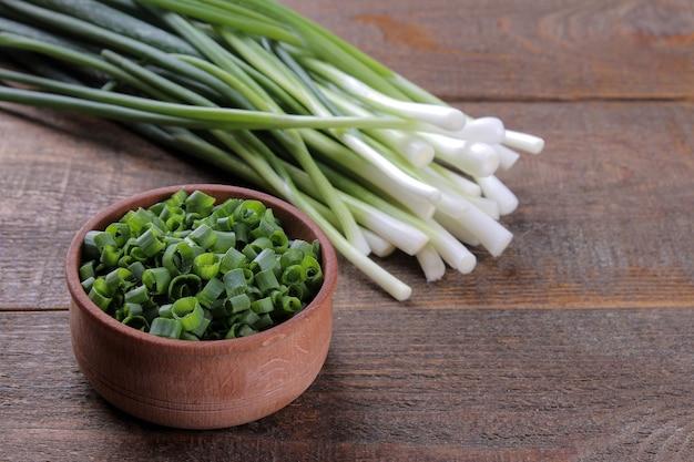 Grüne frische zwiebel und eine holzschale mit geschnittenen zwiebeln auf einem braunen holztisch