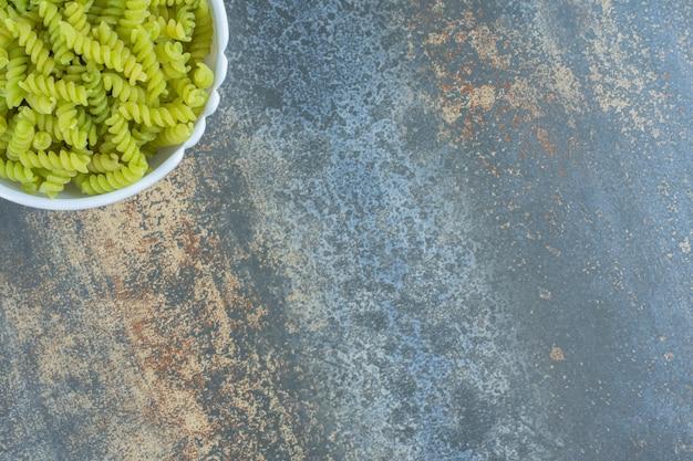 Grüne fusilli-nudeln auf dem marmorhintergrund.
