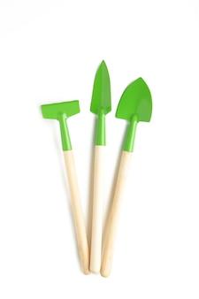 Grüne gartengeräte lokalisiert auf weißer oberfläche