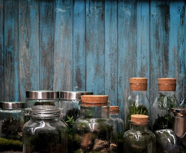 Grüne gartensammlung im gewächshaus der glasflasche im ökologie-hobby auf holzhintergrund auf frischer natur im geheimen gartenkonzept