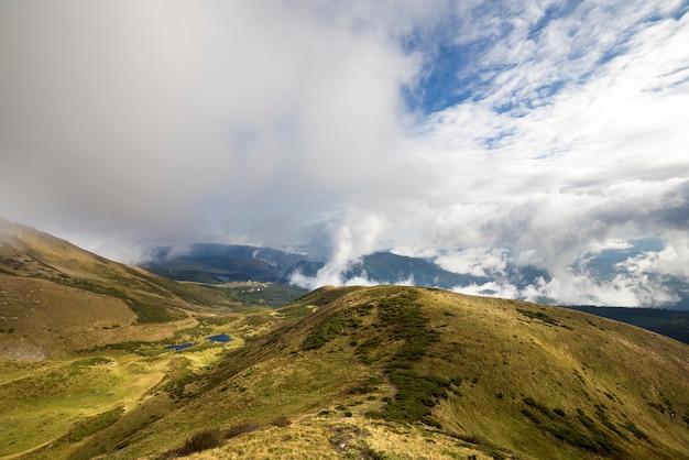 Grüne gebirgspanoramablick auf blauem himmel mit weißen wolken kopieren raumhintergrund am hellen sonnigen tag. tourismus und reisekonzept.