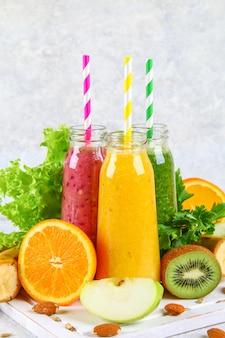Grüne, gelbe, purpurrote smoothies in korinthenflaschen, petersilie, apfel, kiwi, orange auf einer grauen tabelle.