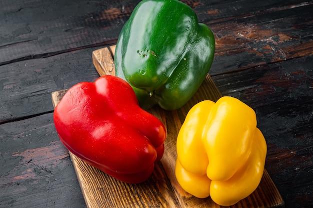 Grüne, gelbe und rote paprika auf altem dunklem holztisch