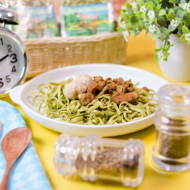 Grüne gemüsenudeln in einer schüssel mit asiatischen frikadellen und indonesischem hühnercurry