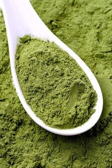 Grüne gemüsepulverbeschaffenheit auf weißem löffel