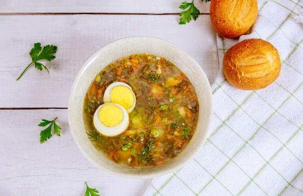 Grüne gemüsesuppe mit ei und knusprigen brötchen