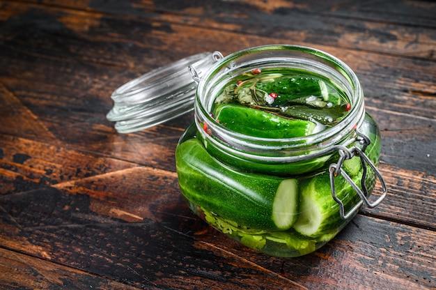 Grüne gesalzene gurken in einem glas. dosen gemüse. dunkler holztisch. draufsicht.