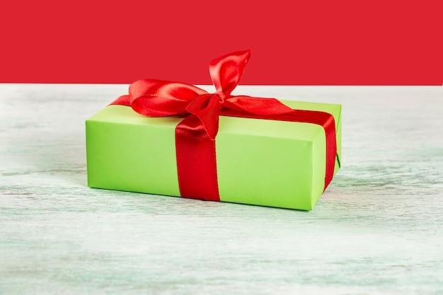 Grüne geschenkbox mit rotem band auf einem hellen holztisch
