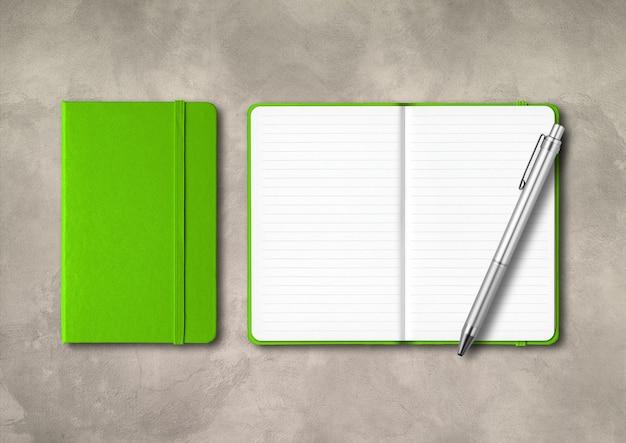 Grüne geschlossene und offene notizbücher mit einem stift. isoliert auf konkretem hintergrund
