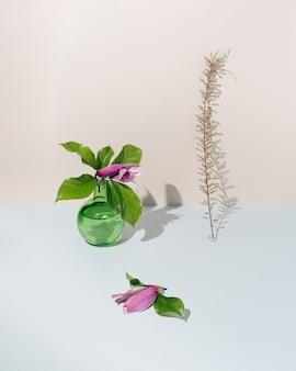 Grüne glasflasche, schöne magnolienblumen und trockene pflanze auf pastellbeigem hintergrund. konzeptionelle minimale szene. ästhetische tapete.