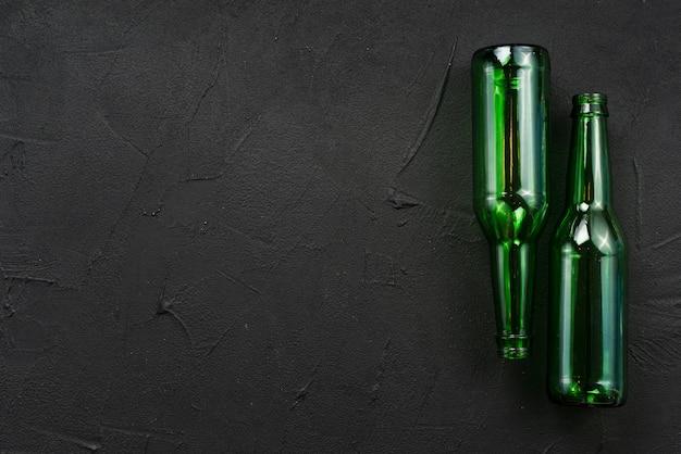 Grüne glasflaschen, die auf schwarzen hintergrund legen
