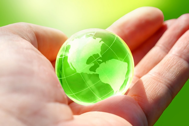 Grüne glaskugel des planeten erde in menschlicher hand