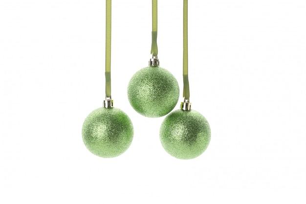 Grüne glitzernde weihnachtskugeln lokalisiert auf weißem hintergrund