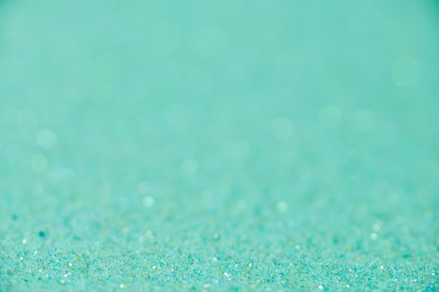 Grüne glitzertextur. neujahrs- oder weihnachtshintergrund für grußkarten. valentinstag feier. glänzendes glitzerdesign für festliche dekoration: hochzeits-, urlaubs- oder jubiläumsfeier.